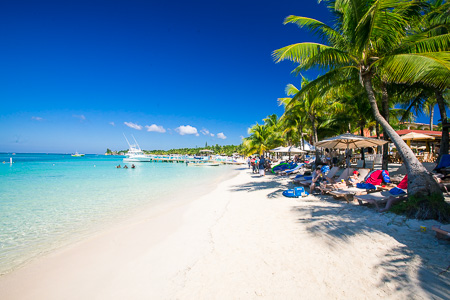 White sand beach and palm trees with a perfect blue sky in West Bay Roatan